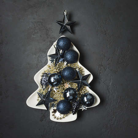 Christmas blue glass balls in plate shape of fir tree on black. Xmas greeting card. View from above.
