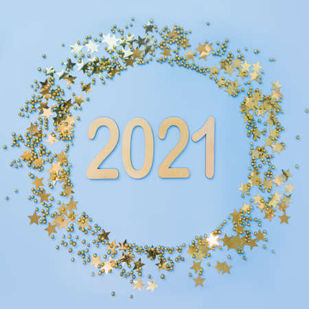 Christmas frame with date New 2021 Year and golden glitter confetti stars on blue. View from above. Xmas circle border. Happy New Year. Stok Fotoğraf