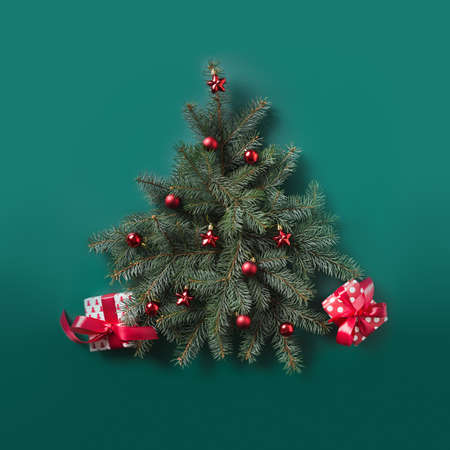 Christmas tree made of fir branches and red balls decorated red gifts on green. Flat lay. Top view. Xmas square greeting card.