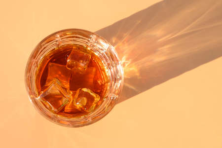 Glass of cold whiskey on beige background with sunny shadow. Copy space. View from above