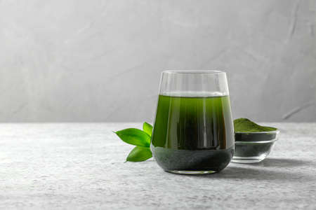 Chlorella healthy detox drink in glass and powder in bowl on a gray background. Close up. Space for design.