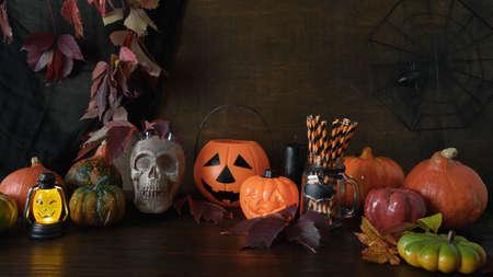 Halloween pumpkins, skull, head jack-o-lantern on dark wooden background. Preparation for fun party. Happy Halloween banner.