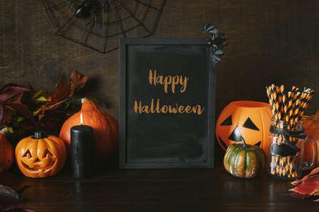 Halloween party background with pumpkins, web, spooky spiders, pumpkin head jack-o-lantern on dark. Text - Happy Halloween on chalkboard.