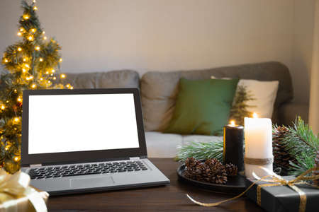 Home interior in living room with laptop, Christmas tree, wooden tabletop with cozy candles. Xmas holiday at home.