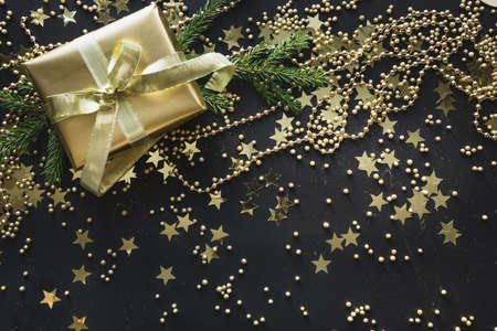 Christmas golden gift and holiday shiny decoration on black background. Happy New Year. Xmas greeting card with copy space. Stockfoto