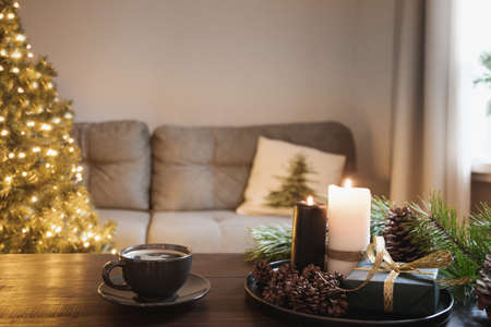 Cozy interior with Christmas tree and warm cup of coffee on wooden tabletop with candles, gifts cones in living room. Xmas holiday at home.
