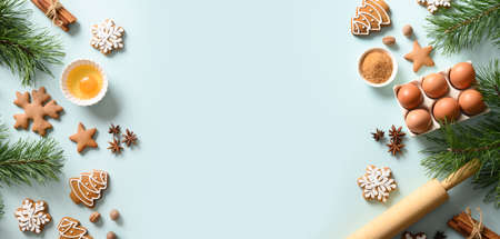 Christmas banner with cookies, different spices, eggs, rolling pin and ingredients for cooking on light blue background. Copy space. View from above.