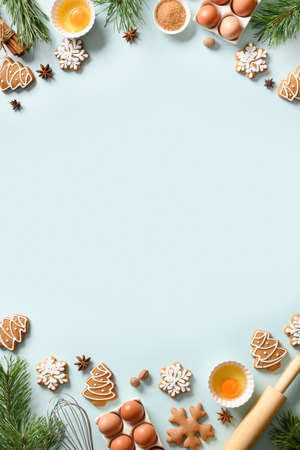 Christmas vertical cooking banner with traditional cookies with ingredients on light blue background. Space for text. View from above.