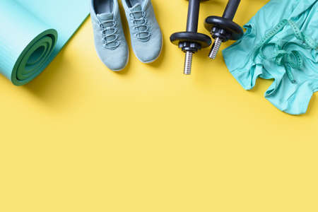 Sport and fitness green equipment, mat, dumbbells, fitness shoes on yellow. View from above, copy space.