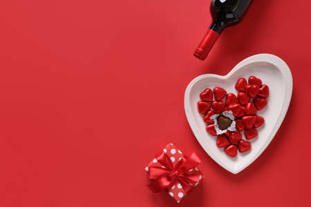 Valentines day composition of gift, red wine, chocolate sweets on red background. Greeting card with copy space. 版權商用圖片