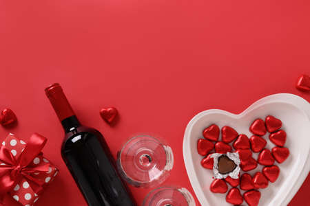 Valentines day composition, gift, wine and hearts chocolate sweets on red background. Romantic invitation with copy space.