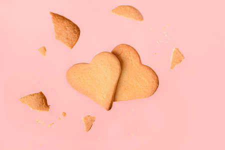 Flying homemade heart shaped cookies on pink background. Valentines day greeting card. Love concept.