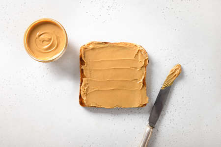 Crispy toast with peanut paste for breakfast on white background. View from above. Archivio Fotografico