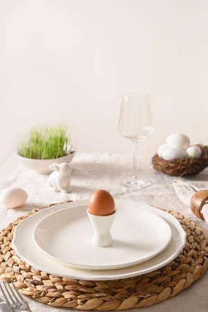 Spring stilish Easter table setting with organic eggs, bunny and blooming flowers.