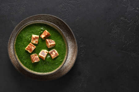 Palak paneer of spinach and cheese on black.