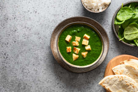 Palak Paneer served with basmati rice on grey. Indian vegetarian cuisine mades of spinach and paneer cheese.