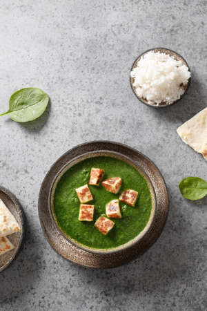 Palak Paneer made of spinach and paneer cheese on grey stone background. Indian cuisine.
