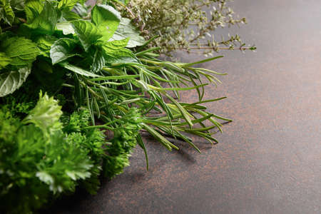 Homegrown fresh parsley, mint ,thyme, rosemary on brown background. Reklamní fotografie - 166666566