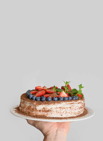 Homemade tasty biscuit cake with mascarpone cheese decorated berries, mint, strawberries and blueberries in hand. Vertical format. Birthday.