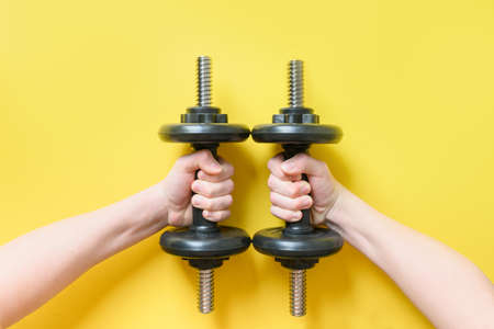 Black dumbbells in hands on yellow. Sport fitness equipment. Reklamní fotografie