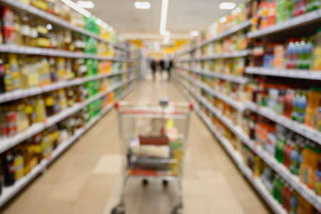 Shelves and cart in supermarket as blurred background.