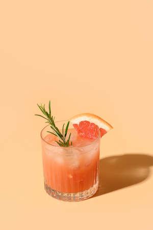 Grapefruit juice garnish rosemary sprig on color beige background. Mocktail Paloma. Reklamní fotografie