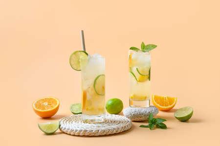 Summer lemonade or cocktail with orange and lime slice on color background. Refreshing drink. Reklamní fotografie