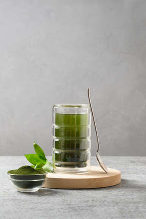 Chlorella healthy beverage on a grey background.