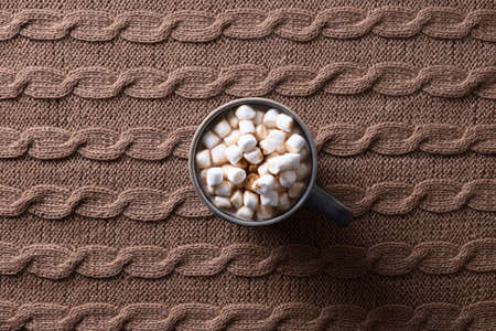 Cup of coffee or cocoa with marshmallow in cozy lifestyle warming scarf on brown background.