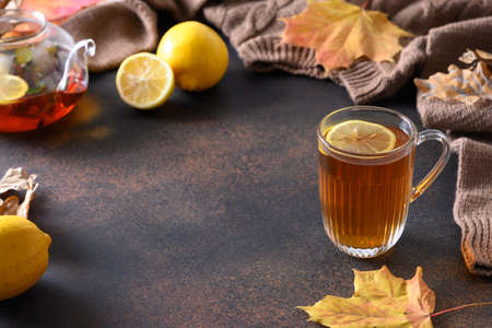 Warming black tea with lemon in cozy lifestyle with fall leaves and cozy scarf.