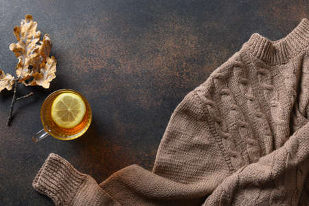 Warming tea with lemon in cozy sweater on brown. Top view with copy space. Reklamní fotografie - 166558748
