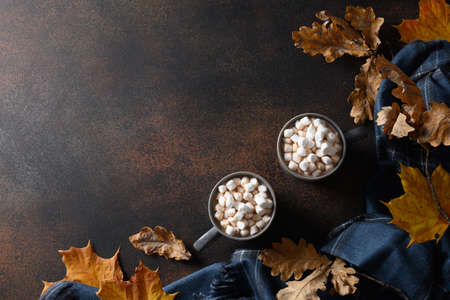 Two cups of coffee or cocoa with marshmallow in cozy lifestyle warming scarf on brown background.