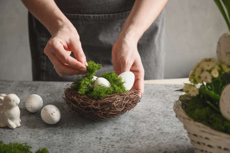Easter floral DIY composition for table centerpiece with white eggs, moss and bunny. Reklamní fotografie