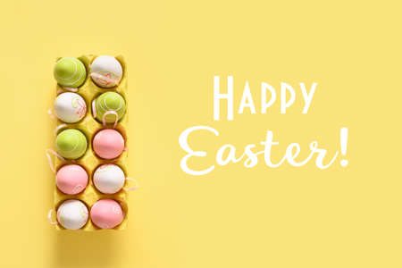 Easter pastel eggs in yellow carton box on yellow.