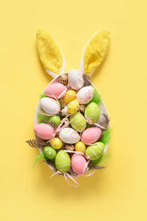 Colorful pastel easter eggs in plate and bunny ears on yellow. Easter greeting card.