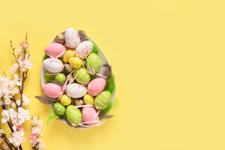Easter pastel eggs and spring blooming flowers.
