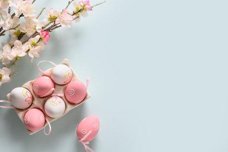 Easter eggs and spring blooming flowers on blue. Reklamní fotografie