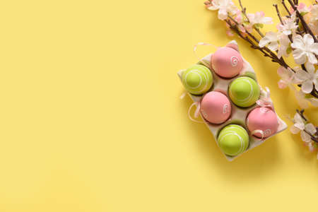 Easter eggs and spring blooming flowers on yellow. Reklamní fotografie