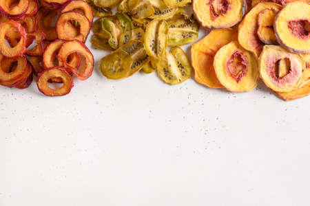Dried sliced plums, kiwi, peach on white. Fall harvest. Home drying. Vegan snack. Reklamní fotografie