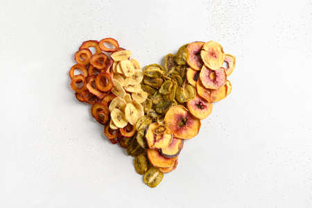 Heart made of dried sliced plums, kiwi, peach chips on white. 版權商用圖片