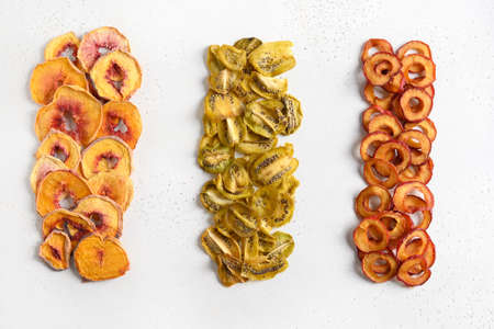 Plums, kiwi, peach chips as food background. Free sugar.