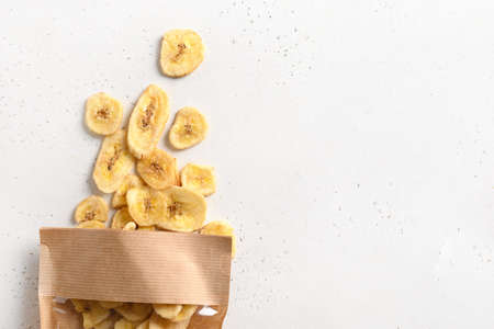 Dried sliced fruits banana chips in paper bag on white. Snack vegan sugarfree food.