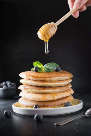 Homemade stack of pancakes with blueberry, honey and mint in modern plate on black. Reklamní fotografie - 167154821