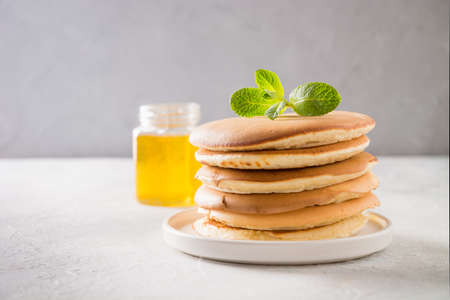Stack of pancakes with pouring honey, fresh blueberry and mint on light background.