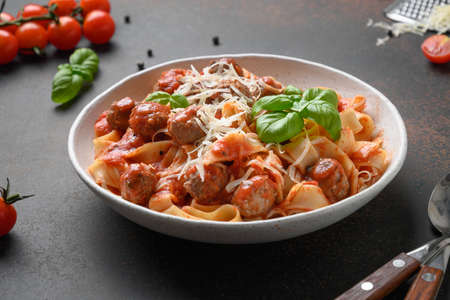 Italian pasta fettuccine with meatballs, cheese, tomatoes, basil.