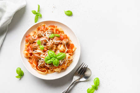 Pasta fettuccine with tomato sauce with basil on white background.