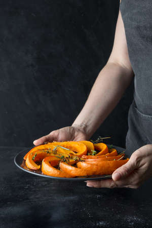 Baked pumpkin with thyme and salt on black in woman hands.