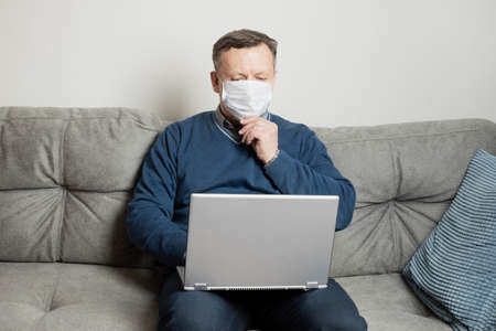 Man in protective medical mask work at home by laptop. Remote work. Quarantine. Home office. 版權商用圖片