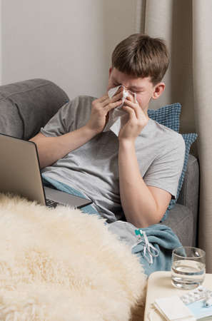 Teenager tries to study online and sneezes into paper towel. Self isolation. Quarantine. Distance elearning.