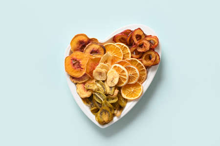 Dried sliced plums, kiwi, peach fruits chips in plate shape of heart on blue background, home drying. Snack vegan free sugar food. View from above. 版權商用圖片